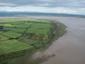 Eroded edge of the saltmarsh at Cardurnock, with Moricambe Bay beyond and the Lakeland fells; the masts of Anthorn to the right